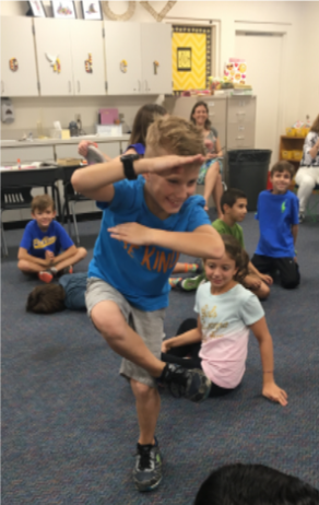 A 3rd grade student from Pine View Elementary joyfully uses his body to show symbols and numbers within a number sentence.